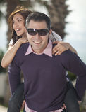 Young man piggybacking his girlfriend. Under palm tree smiling to the camera, selective focus on woman Stock Photos