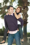 Young man piggybacking his girlfriend. Under palm tree smiling to eachother, selective focus on male Royalty Free Stock Image