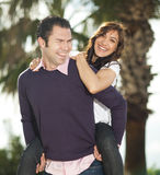 Young man piggybacking his girlfriend. Under palm tree smiling, selective focus on woman Royalty Free Stock Image