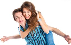 Young man piggybacking his girlfriend. Smiling young men piggybacking his pretty girlfriend. Isolated on white background Royalty Free Stock Photography