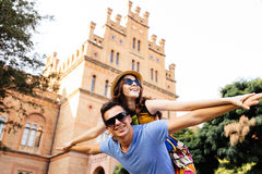 Young man piggybacking his girlfriend while keeping arms outstretched Stock Photography