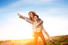 Young man piggybacking his happy girlfriend with raised hand. Cheerful lovers dreaming Stock Images