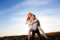 Young man piggybacking his happy girlfriend with raised hand. Cheerful lovers dreaming Royalty Free Stock Image