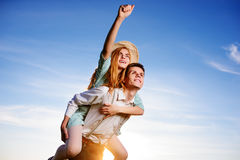 Young man piggybacking his happy girlfriend with raised hand. Cheerful lovers dreaming stock photography