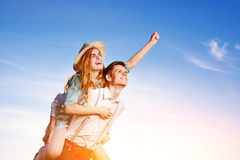 Young man piggybacking his happy girlfriend with raised hand. Cheerful lovers dreaming Royalty Free Stock Photography