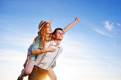 Young man piggybacking his happy girlfriend with raised hand. Cheerful lovers dreaming Royalty Free Stock Images