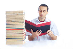 Young man with a pile of books reading one of them Stock Photos