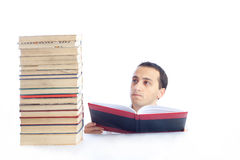 Young man with a pile of books reading one of them Stock Images