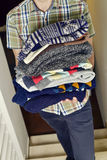 Young man with a pile of folded sweaters Stock Image