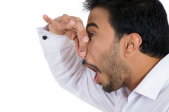 Young man pinching his nose with disgust on his face as something stinks Royalty Free Stock Images