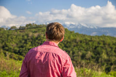 Young man in pink shirt from back enjoying beautiful mountain vi Stock Photos