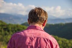 Young man in pink shirt from back enjoying beautiful mountain vi. Ew Stock Photo