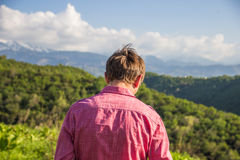 Young man in pink shirt from back enjoying beautiful mountain vi. Ew Royalty Free Stock Image
