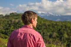 Young man in pink shirt from back enjoying beautiful mountain vi. Ew Royalty Free Stock Images