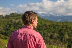 Young man in pink shirt from back enjoying beautiful mountain vi. Ew Stock Images