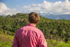 Young man in pink shirt from back enjoying beautiful mountain vi. Ew Royalty Free Stock Photo