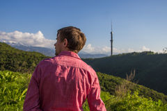 Young man in pink shirt from back enjoying beautiful mountain vi. Ew, Almaty, Kok Tobe Stock Images