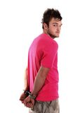 Young man in pink shirt with handcuffs Royalty Free Stock Images