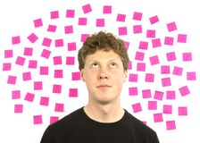 Young man with pink sticky notes question marks de Royalty Free Stock Photography