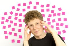 Young man with pink sticky notes question marks de Royalty Free Stock Photos