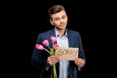 Young man with pink tulips and sorry sign hopefully looking at camera Stock Photo
