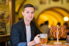 Young man with pint of beer and salted soft pretzels in beer sport bar. Closeup salted soft pretzels and beer on wooden background stock photography
