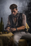 Young Man in Pirate Fashion Outfit Looking at Gold in Hand Stock Photography