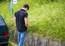 Young Man Pissing at the Grassy Roadside Royalty Free Stock Image