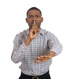 Young man placing finger on lips as if to say ssshhh Stock Photo