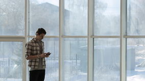 A young man in a plaid shirt and a clock on hand, looking at smartphone screen, standing beside a panoramic window with. A winter landscape. He is dressed in a stock footage