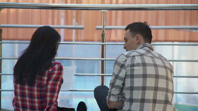 Young man in a plaid shirt conveys the woman on paper contract. stock video