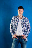 Young man with plaid shirt denim jeans in blue. Handsome young man with plaid shirt denim jeans in blue background Royalty Free Stock Photography