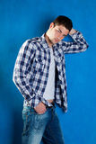 Young man with plaid shirt denim jeans in blue. Handsome young man with plaid shirt denim jeans in blue background Stock Photos