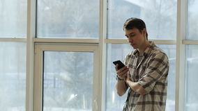 A young man in a plaid shirt stands in front of panoramic windows and keep smartphone in hand. stock video footage