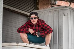 Young man in plaid shirt and sunglasses in brick industrial alle. Millennial in hat and sunglasses acting tough in alley Royalty Free Stock Images