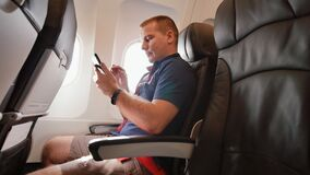 A young man in the plane before departure writes the text in his mobile phone. A young man in the plane before departure writes the text in his mobile phone stock video footage