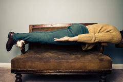 Young man in plank position on old sofa Stock Photo