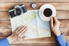 Young man planning vacation journey with map. Holidays and tourism concept. Closeup of young adult planning vacation journey with map at home or cafe Royalty Free Stock Photos