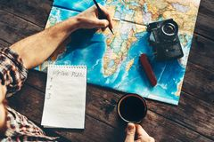 Young Man Is Planning Vacation Travel With Map, Top View. He Drinks Coffee And Marks. Travel Concept Royalty Free Stock Images