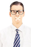 Young man with plaster on his mounth gesturing silence Stock Image