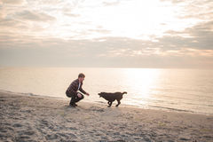 Young man play with dog. Young caucasian male walking with dog on the morning beach, sunset on the sea or ocean and man with black labrador puppy Royalty Free Stock Images