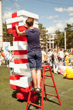 Young man play giant jenga game outdoors using a ladder stock photo