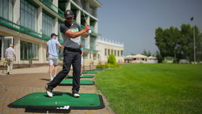 The young man play golf near th clubhouse stock footage