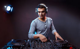 Young man play music on a dj`s mixer at studio. Portrait of confident young DJ with stylish haircut and headphones on head mixing music on mixer on dark Royalty Free Stock Images