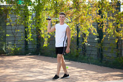 Young man play tennis outdoor on orange court stock photography