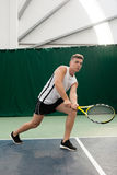 Young man play tennis outdoor on orange court royalty free stock image