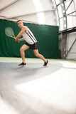 Young man play tennis outdoor on orange court royalty free stock photo