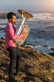 Young man play the trumpet on rocky sea coast during surf. Tuba - instrument. Young man play the trumpet on rocky sea coast during surf Royalty Free Stock Image