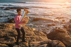 Young man play the trumpet on rocky sea coast during surf. Royalty Free Stock Image