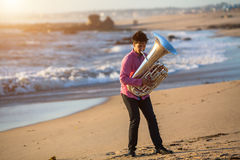 Young man play Tuba musical instrument on sea shore outdoor. Concert. Royalty Free Stock Photo